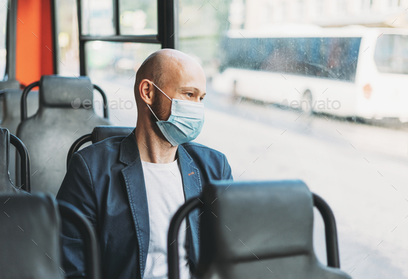 Adult bald bearded man in medical face mask looking out the window in bus - Stock Photo - Images