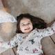 Little funny brunette girl in cozy pajamas with Lollipop in children bed room - PhotoDune Item for Sale