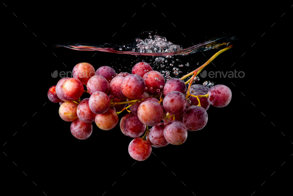 Isolated Red grapes splashing and sinking in water on black background - Stock Photo - Images