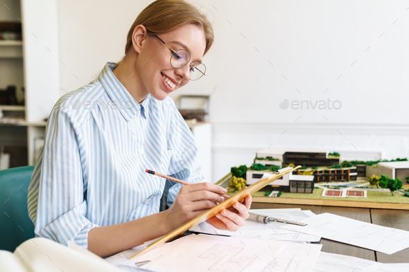 Photo of woman architect working with drawings while designing draft - Stock Photo - Images