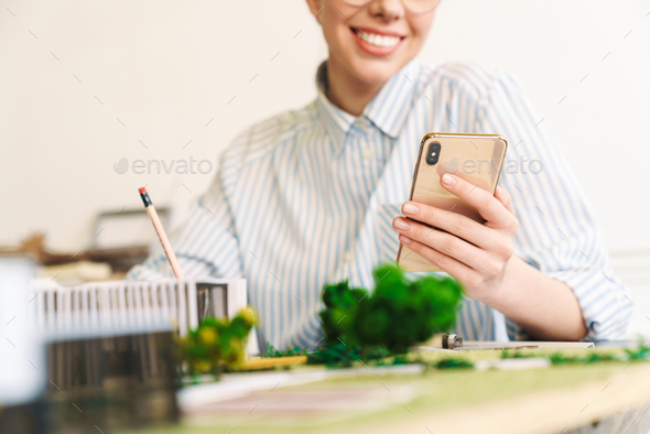 Cropped photo of woman architect using cellphone while designing draft - Stock Photo - Images