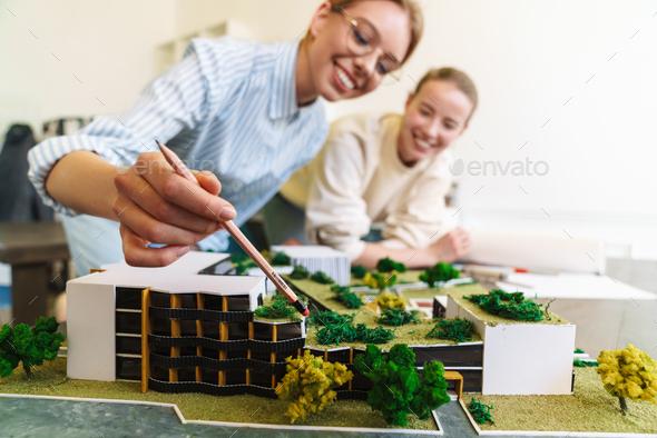 Photo of joyful young women architect designing draft with house model - Stock Photo - Images