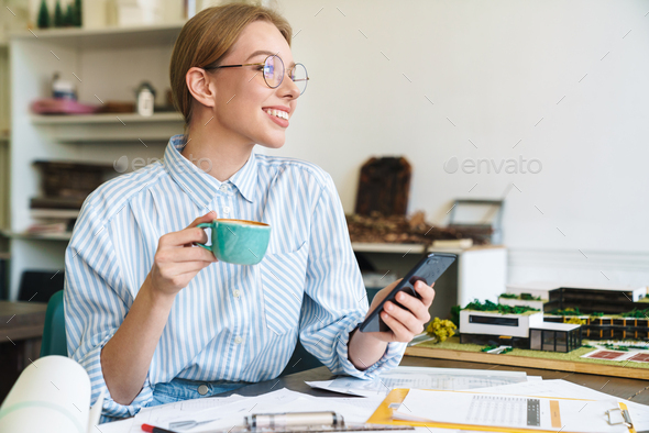Photo happy nice woman architect drinking coffee and using mobile phone - Stock Photo - Images