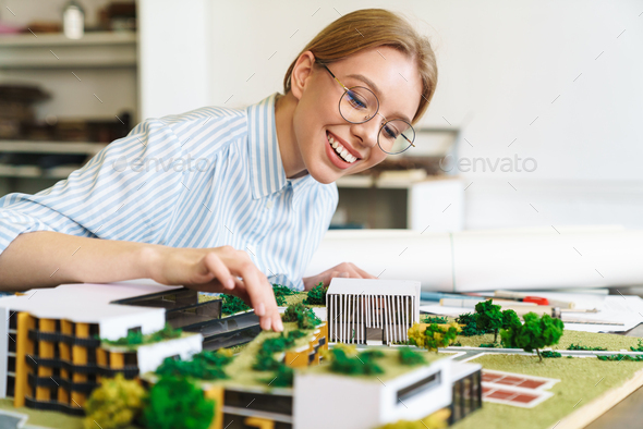 Photo of joyful young woman architect designing draft with house model - Stock Photo - Images