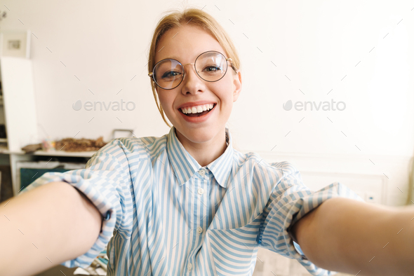 Photo of happy blonde woman smiling while taking selfie photo - Stock Photo - Images