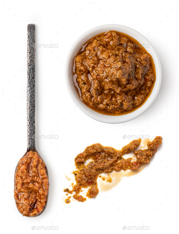 Bowl and spoon with red pesto sauce - Stock Photo - Images