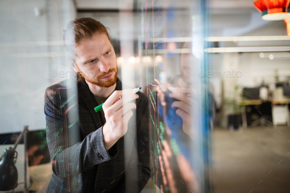 Handsome man working and writing on glass board in office. Business, technology, research concept - Stock Photo - Images