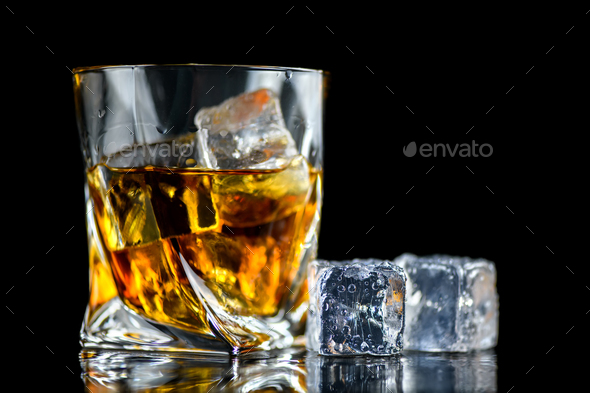 Glass of whiskey with cube ice on black background - Stock Photo - Images