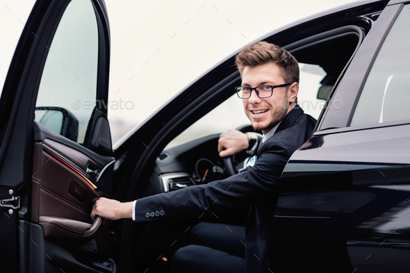 Young businessman driving alone in his luxury car - Stock Photo - Images