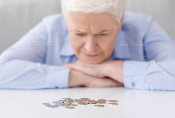 Elderly Poverty. Depressed senior woman looking at last coins lying at table - Stock Photo - Images