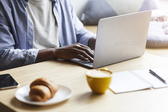 African American blogger working with laptop while having breakfast in cafe, closeup - Stock Photo - Images