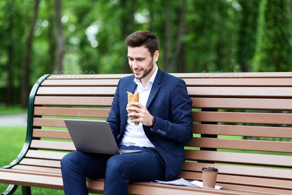 Happy businessman with laptop having lunch on bench at city park - Stock Photo - Images