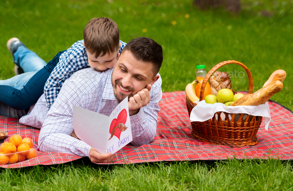 Best Father's Day greeting. Father and son with card cuddling on plaid in park during picnic - Stock Photo - Images