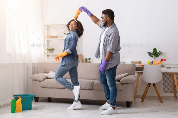 Loving African American Couple Dancing While Cleaning Flat Together - Stock Photo - Images