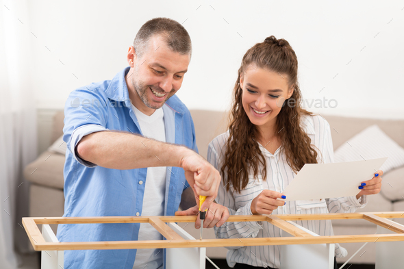 Cheerful Spouses Assembling Furniture Installing Cabinet Furnishing Home Sitting Indoor - Stock Photo - Images