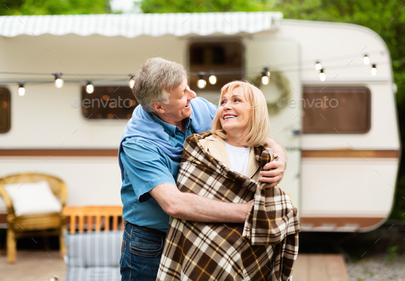 Caring senior man covering his beloved woman with blanket near motorhome at camping site - Stock Photo - Images