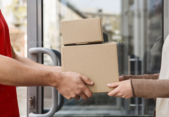 Guaranteed excellent service. Hands of client and courier are holding parcels - Stock Photo - Images