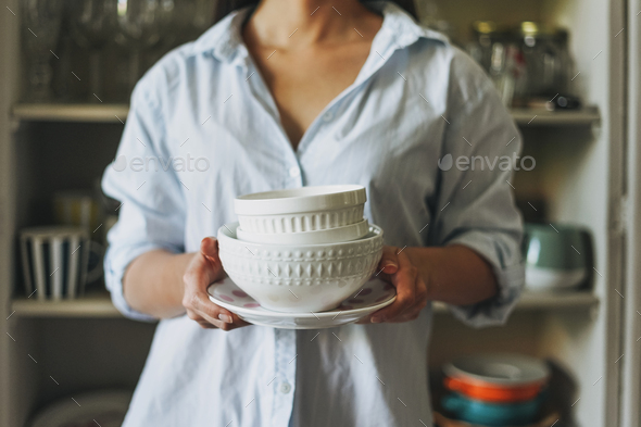 Crop photo of young woman in casual shirt with dishes near vintage sideboard at home - Stock Photo - Images