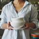 Crop photo of young woman in casual shirt with dishes near vintage sideboard at home - PhotoDune Item for Sale
