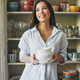 Young asian woman in casual shirt with dishes near vintage sideboard at home - PhotoDune Item for Sale