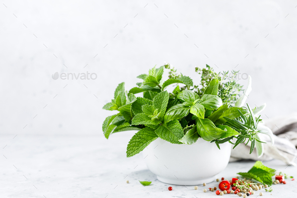 Bunch of aromatic herbs in mortar on kitchen table - Stock Photo - Images