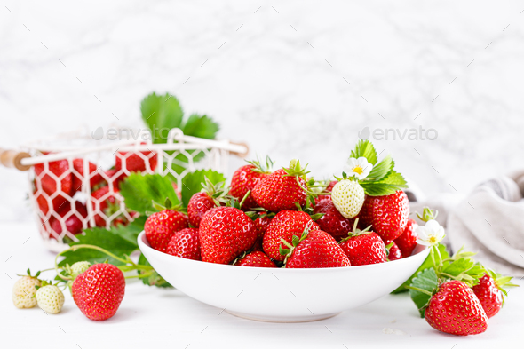 Strawberry on plate with twigs and leaves on white  background - Stock Photo - Images