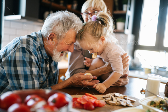 Happy smiling senior randparents playing with their granddaughter - Stock Photo - Images
