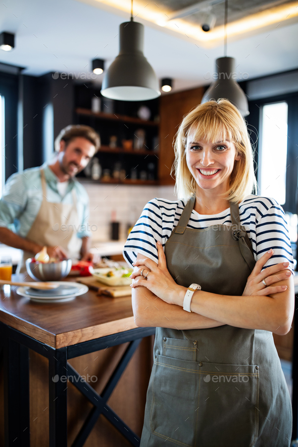 Beautiful young couple is talking and smiling while cooking healthy food in kitchen at home - Stock Photo - Images