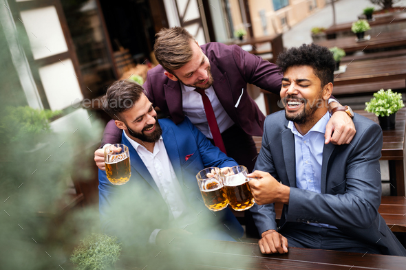 Happy young businessmen drinking beer and talking at pub after work - Stock Photo - Images
