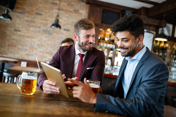 Happy young businessmen in suits are smiling and talking in a restaurant - Stock Photo - Images