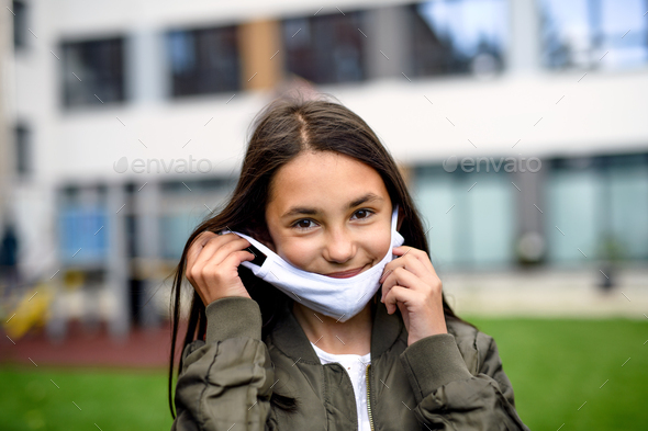 Portrait of happy child with face mask going back to school after covid-19 lockdown - Stock Photo - Images
