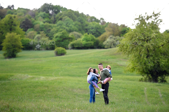 Happy family with two small daughters standing outdoors in spring nature - Stock Photo - Images