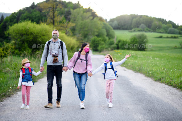 Family with two small daughters on trip outdoors in nature, wearing face masks - Stock Photo - Images