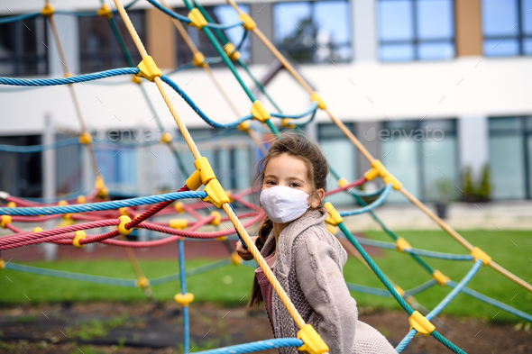 Portrait of happy child with face mask on playground after covid-19 lockdown - Stock Photo - Images