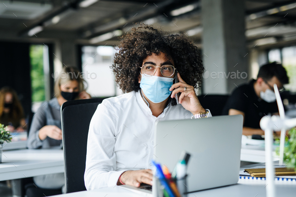 Portrait of young man with face mask back at work in office after lockdown - Stock Photo - Images