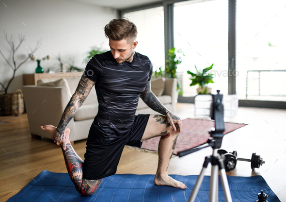 Man trainer doing online workout exercise indoors at home, using camera - Stock Photo - Images