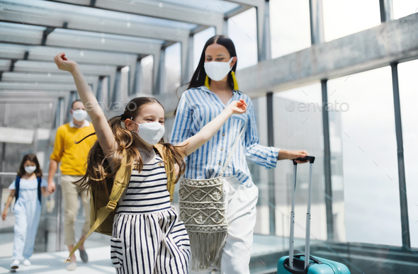 Family with two children going on holiday, wearing face masks at the airport - Stock Photo - Images