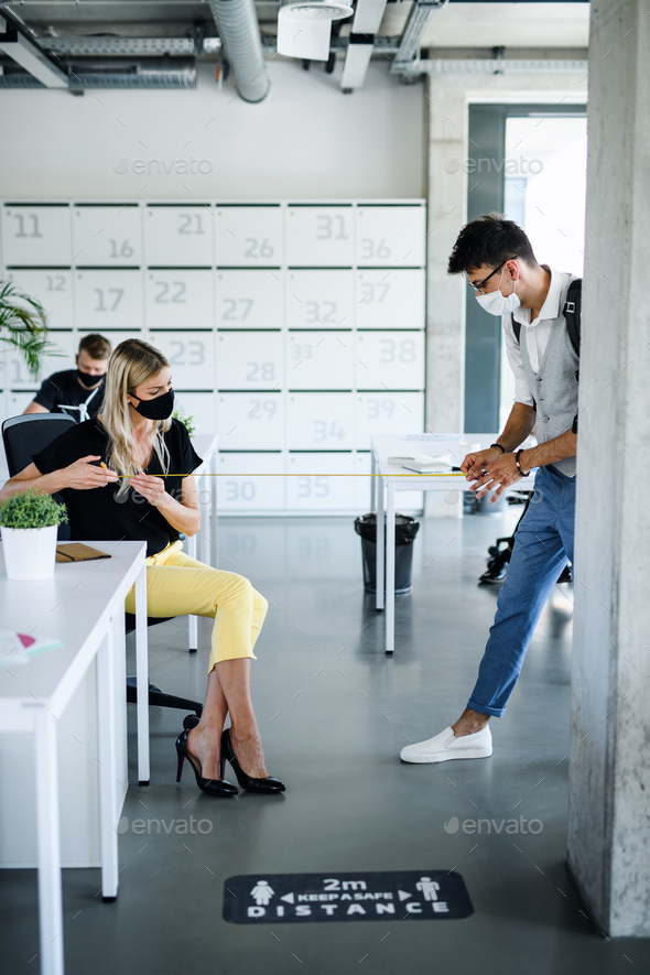 Young people with face masks back at work in office after lockdown, measuring distance - Stock Photo - Images