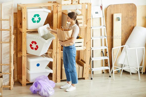 Woman sorting waste in bins - Stock Photo - Images