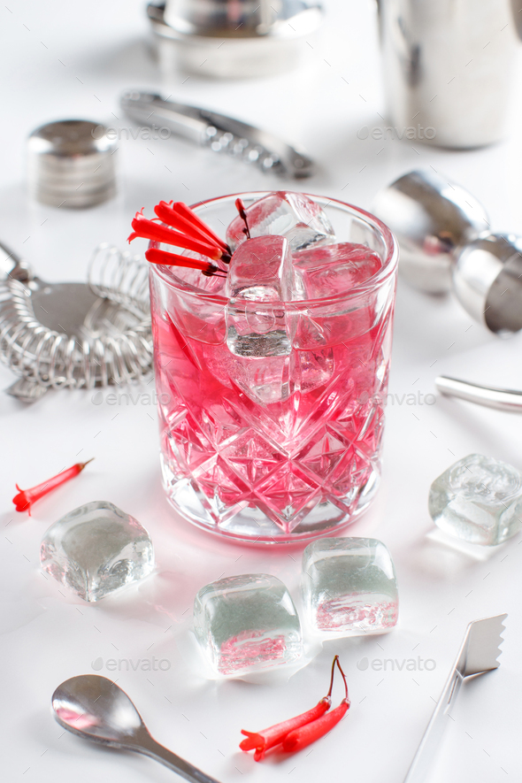 Cosmopolitan cocktail in a glass decorated with pink flowers - Stock Photo - Images