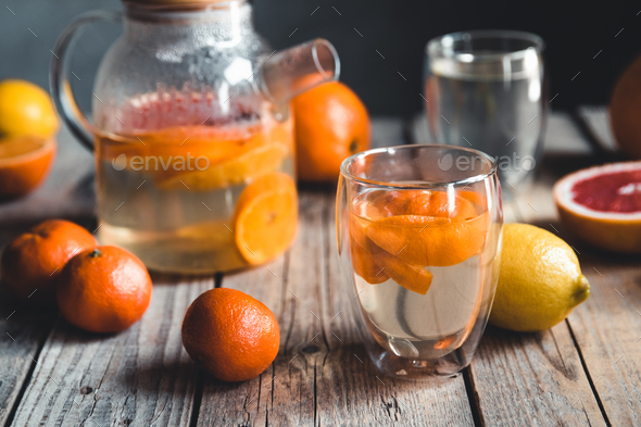 Citrus tea in a transparent teapot on a table with grapefruit and on a wooden table. Healthy drink - Stock Photo - Images