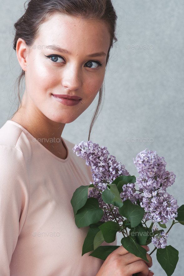 Woman with lilac brunch over gray background. Studio shot. - Stock Photo - Images