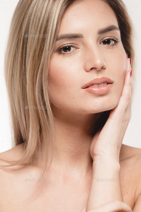 Beautiful woman touching her face by fingers. face portrait close up blonde. Studio shot. - Stock Photo - Images
