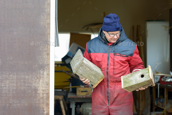Mature handsome man making bird house indoors - Stock Photo - Images