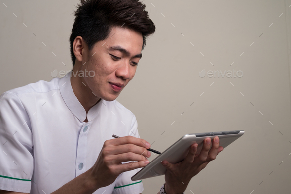 Portrait of young handsome Asian man - Stock Photo - Images