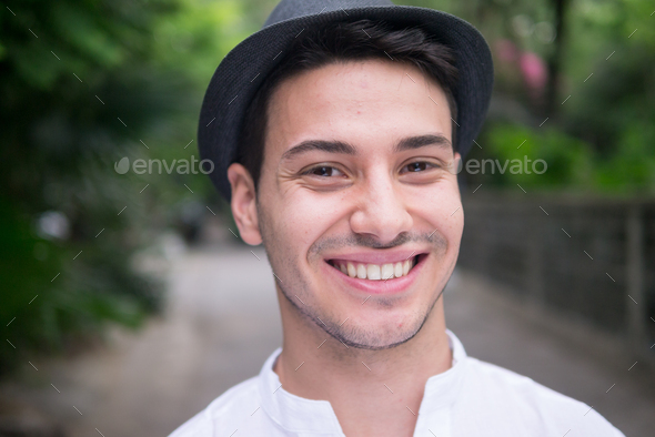 Portrait of young handsome man at the park - Stock Photo - Images