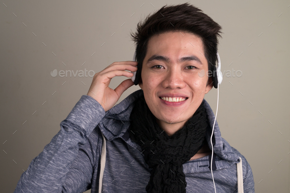 Portrait of young handsome Asian tourist man - Stock Photo - Images