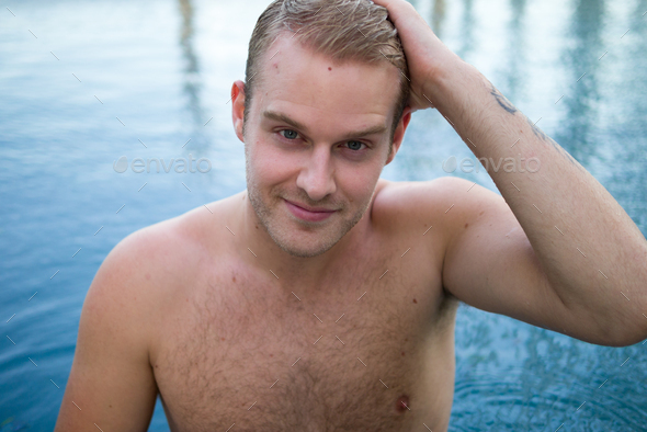 Young handsome shirtless man with blond hair in the swimming pool - Stock Photo - Images