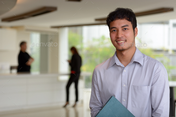 Young Asian businessman inside the office building - Stock Photo - Images