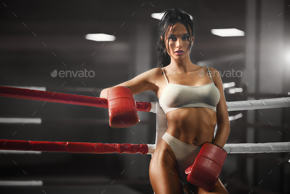 Female boxer leaning on rope - Stock Photo - Images